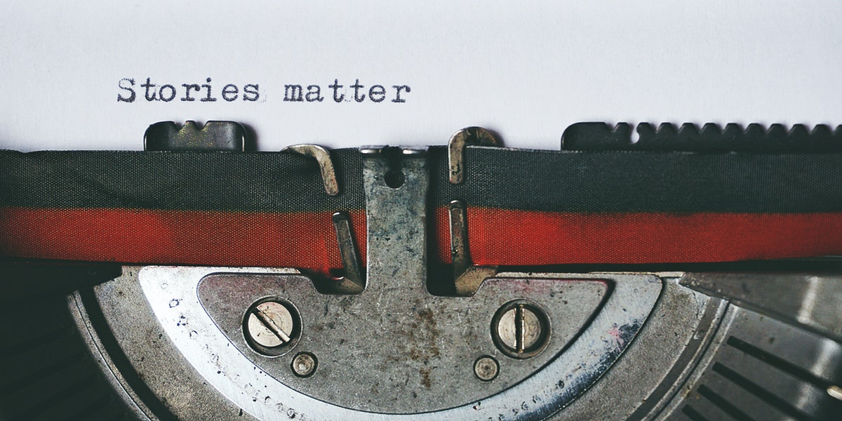 A piece of paper in a typewriter with the words, ' stories matter' typed on it.