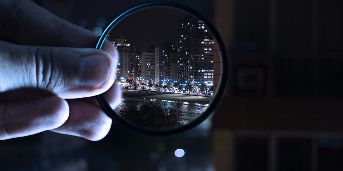 handing holding magnifying glass to city night skyline
